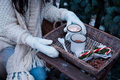 Two cups of hot cocoa in a wicker basket on a wooden table. Stock Image