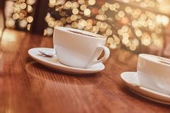 Two cups of hot coffee with art on the wooden table in a coffee shop, blur background with bokeh effect royalty free stock image