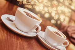 Two cups of hot coffee with art on the wooden table in a coffee shop, blur background with bokeh effect royalty free stock photography