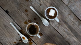 Two cups of hot coffee. The camera slide over two cups of hot coffee with marshmallows and cookies on wooden background, top view, close up stock video footage