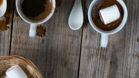 Two cups of hot coffee. The camera slide over two cups of hot coffee with marshmallows and cookies on wooden background, top view, close up stock video