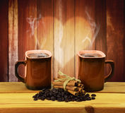 Two cups of hot coffee, cinnamon and coffee beans. Communication Stock Images