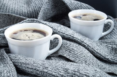 Two cups of hot coffee in the folds of a gray scarf Stock Photo