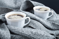 Two cups of hot coffee in the folds of scarf Stock Photo