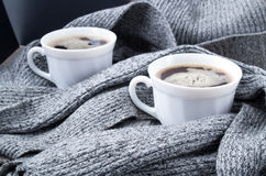 Two cups of hot coffee in the gray scarf Royalty Free Stock Photos