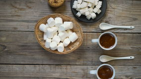 Two cups of hot coffee. With marshmallows and cookies on wooden background, top view, close up stock video footage