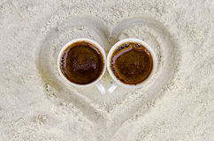 Two cups with hot coffee. On sand Stock Photos