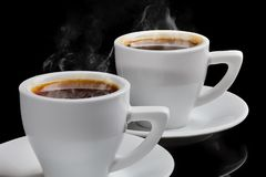 Two cups of hot coffee with steam on a black background Royalty Free Stock Images