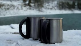 Two Cups of Hot Coffee or Tea in Snowy Winter. Two Cups of Hot Coffee or Tea standing on the Outdoor in Snowy Winter Morning. Slow motion stock video footage