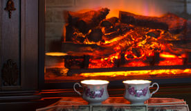 Two cups of hot drink near fireplace. Stock Photo