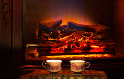 Two cups of hot drink near fireplace. Royalty Free Stock Photography