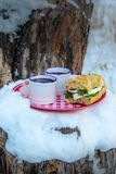 Two cups of hot mulled wine on a plate in a snowy forest. Two cups of hot mulled wine and sandwich with cheese and herbs on a red plate in a snowy forest Stock Images