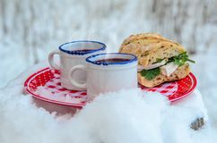 Two cups of hot mulled wine on a plate in a snowy forest. Two cups of hot mulled wine and sandwich with cheese and herbs on a red plate in a snowy forest Royalty Free Stock Photo