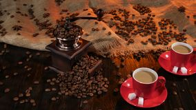 Two cups of latte with pieces of sugar on saucer. Coffee grinder filled with coffee beans, wooden table laid out with burlap and covered with coffee beans and stock video footage