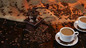 Two cups with latte on saucer with the coffee beans. Mugs and saucers white color, coffee grinder filled with coffee beans, wooden table laid out with burlap stock video