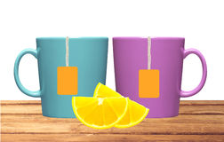Two cups, lemon and tea bags with orange label on table  Stock Photo