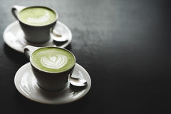 Two cups of matcha latte on black table Royalty Free Stock Image