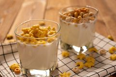 Two cups of milk with cereal rings insunny morning as healthy breakfast. Two cups of milk with cereal rings in a sunny morning as healthy breakfast stock images