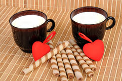 Two cups with milk, thin hearts Stock Photo