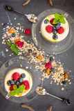 Two cups with natural yogurt with fresh berries and muesli, cere Stock Photo