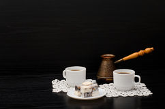 Two Cups Of Coffee On White Napkins, Pots And Turkish Sweets On A Black Background. Royalty Free Stock Image