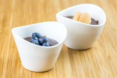 Two cups of pudding with blueberries and biscuit Stock Photography