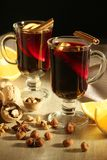 Cups with mulled wine. Two cups with ready mulled wine with anise, cinnamon and nuts around royalty free stock photography