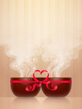 Two cups with red heart-shaped bow. Two ceramic cups, tied together by red ribbon with heart-shaped bow, light steam on wooden background. Pleasant pastime for Stock Image