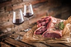 Two cups with red wine and raw beef steak on wooden table stock photos