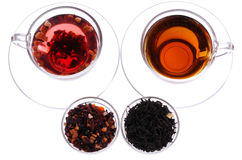 Two cups and saucers with black and fruit tea. Two transparent cups and saucers with black and fruit tea Stock Photos