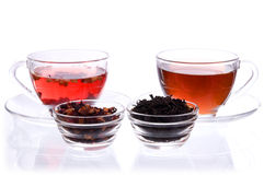 Two cups and saucers with black and fruit tea. Two transparent cups and saucers with liquid and dry black and fruit tea Stock Photo