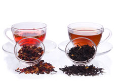 Two cups and saucers with black and fruit tea. Two transparent cups and saucers with liquid and dry black and fruit tea Royalty Free Stock Images