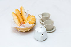Two cups on saucers teapot wicker straw basket with bread light breakfast Stock Photos