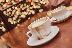 Two cups with spilled coffee on the wooden table in a coffee shop, blur background with bokeh effect royalty free stock images