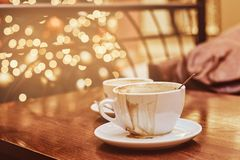 Two cups with spilled coffee on the wooden table in a coffee shop, blur background with bokeh effect royalty free stock photos