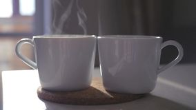 Two cups of steaming coffee stand on the table. Slowmotion. 1920x1080