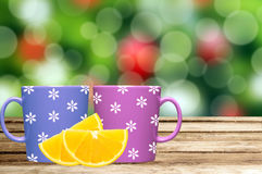 Two cups on table with lemon slice over christmas holiday lights Royalty Free Stock Images