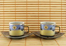Two cups of tea. On the striped rug royalty free stock image