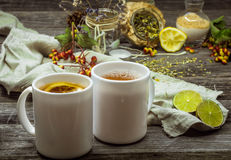Two cups of tea on a beautiful wooden background with lemon and herbs, winter ,autumn Stock Image
