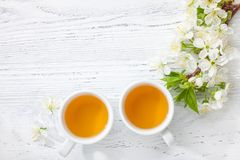 Two cups of tea and branch of blossom cherry on white wooden table.  Stock Images