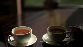 Two cups of tea in a cafe on a wooden table stock footage