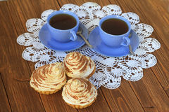 Two cups of tea and cakes on a white tablecloth. On a dark wooden table Royalty Free Stock Images