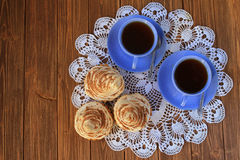 Two cups of tea and cakes on a white tablecloth. On a dark wooden table . Top view Royalty Free Stock Images