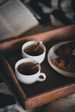 Two cups of tea with cinnamon sticks and anise stars and two croissants on a plate Stock Photo