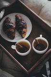 Two cups of tea with cinnamon sticks and anise stars and two croissants on a plate Royalty Free Stock Photo