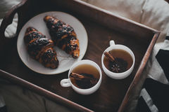Two cups of tea with cinnamon sticks and anise stars and two croissants on a plate Royalty Free Stock Photos