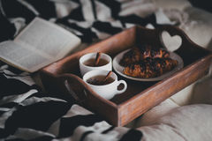 Two cups of tea with cinnamon sticks and anise stars and two croissants on a plate Royalty Free Stock Images