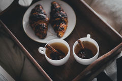 Two cups of tea with cinnamon sticks and anise stars and two croissants on a plate Stock Images