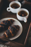 Two cups of tea with cinnamon sticks and anise stars and two croissants on a plate Royalty Free Stock Photography