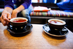 Two cups of tea. Closeup of two cups of tea on wooden table with one being held by hand of woman sitting on cafe bench Royalty Free Stock Image